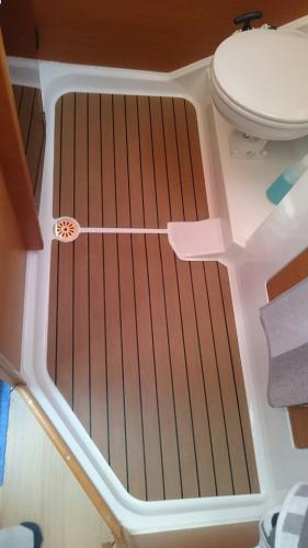 Un-margined boat decking in the toilet of a sailing boat